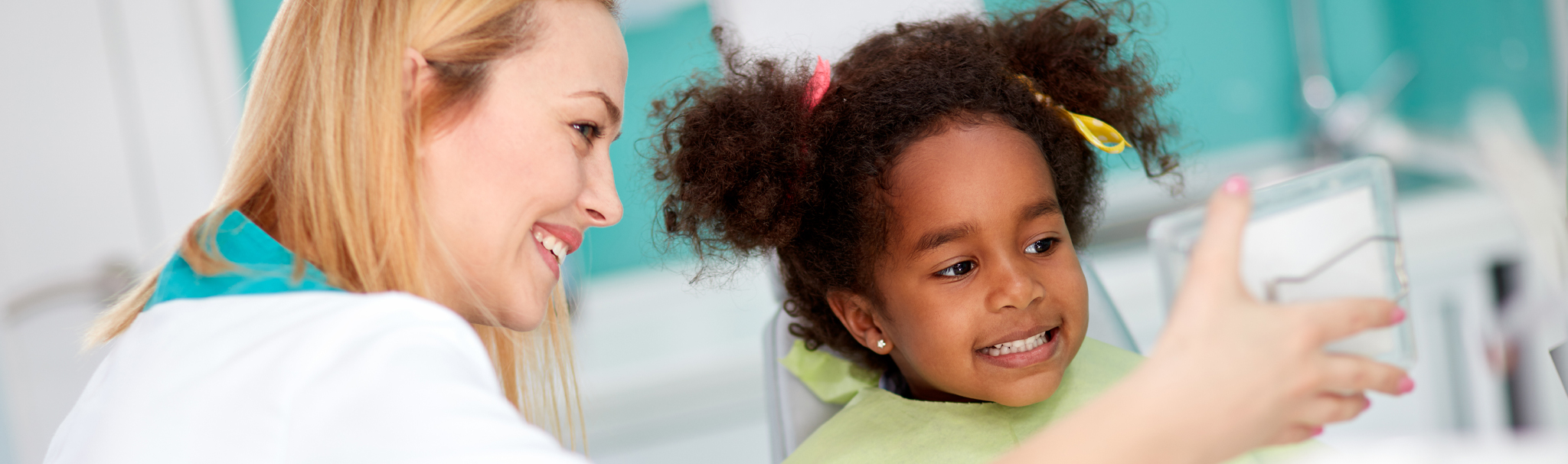 child with dentist smiling in a mirror